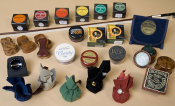 Several brands of violin rosin around a violin bow