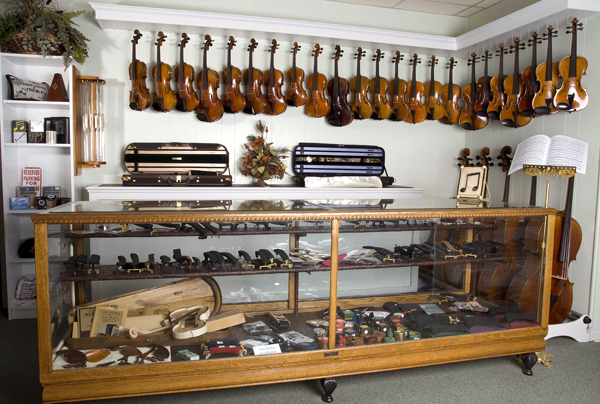 Sapp Violin Shop in Batavia, IL with several violins, violas and cellos behind a glass case with accessories