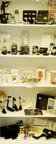 Shelf of violin accessories and gifts including metronomes, music lights and cards